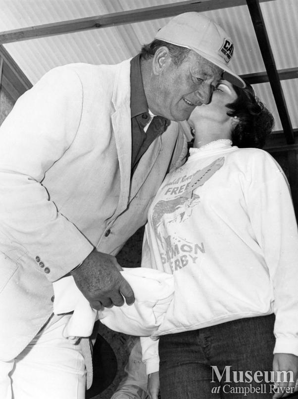 Actor John Wayne gets kiss from Susan Poskitt at Salmon Derby