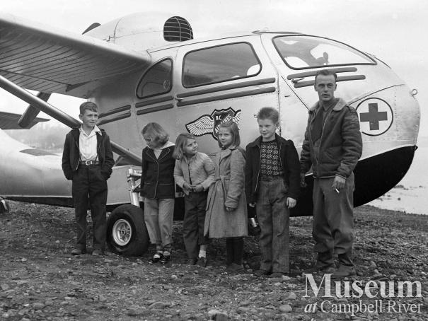 Group of children with pilot beside BC Airlines airplane